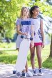 Conceptos del adolescente Dos novias adolescentes así como Longboard al aire libre en parque Imagen de archivo