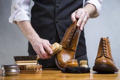 Conceptos del calzado El primer de sirve las manos que limpian el becerro de lujo Le Imagen de archivo