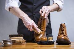 Conceptos del calzado El primer Mans da los zapatos de la limpieza Foto de archivo libre de regalías