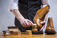 Conceptos del calzado El primer Mans da los zapatos de la limpieza Imagen de archivo libre de regalías
