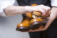 Conceptos del calzado El primer Mans da los zapatos de la limpieza Fotografía de archivo