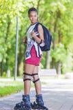 Conceptos del deporte Adolescente afroamericano joven que presenta en los pcteres de ruedas al aire libre en área del parque Imagen de archivo