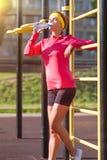 Conceptos del deporte, de la aptitud y del entrenamiento Atleta de sexo femenino caucásico atractivo sonriente en agua potable de Foto de archivo libre de regalías