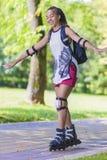 Conceptos del deporte y de la forma de vida Adolescente afroamericano que aprende patinaje sobre ruedas mientras que equilibra co Fotos de archivo