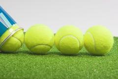 Conceptos del tenis: cuatro pelotas de tenis cerca de un envase mienten en g Imagen de archivo libre de regalías