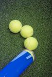 Conceptos del tenis: tres pelotas de tenis cerca de una mentira del envase encendido Imágenes de archivo libres de regalías