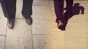 Concepts of continue or quit; stay or walk away; stop or go. Man is standing and walking away; taken from knees down; wearing black trousers and brown shoes Royalty Free Stock Photos