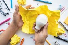 Concepts de créativité d'inspiration avec l'ampoule dans la boule chiffonnée de papier sur la main masculine Solution d'id?es d'a photo stock
