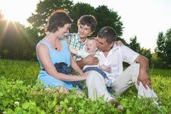 Concepts de la famille Jeune famille caucasienne de quatre personnes posant ensemble dehors Image libre de droits