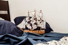 Concepts des affaires et de la créativité le modèle d'un bateau de navigation navigue dans une literie bleue image libre de droits