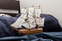 Concepts des affaires et de la créativité modèle d'un bateau de navigation dans une literie bleue Cauchemar ou rêve étrange photo libre de droits