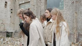 Concepts making their way in the ruins. Young woman making their way through the crowd in the ruins in a slow motion. Female students infringe upon a girl stock footage