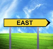 Conceptual arrow sign against beautiful landscape with text - EAST stock photography