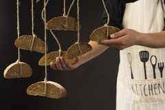 Conceptual art photography of a old woman hands holds pieces of. Bread hanging on the ropes, tied with twine. Copy space. Advertising, cooking, bakery and Stock Photography