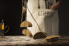 Conceptual art photography of a old woman hands holds the pieces. Of bread hanging on the ropes tied with twine over the old wooden table. Copy space Royalty Free Stock Photography