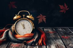 Free Conceptual Autumn Composition. Gold Alarm Clock Wrap Knitted Scarf On A Wooden Vintage Table And Decorated With Maple Leaves. Stock Image - 191915811