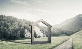 Conceptual background image of concrete home sign on green grass. House stone figure as symbol of real estate outdoors against natural landscape royalty free stock images