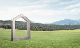 Conceptual background image of concrete home sign on green grass Royalty Free Stock Photo