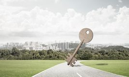 Conceptual background image of concrete key sign on asphalt road. Key stone figure as symbol of access outdoor against natural landscape Stock Photography
