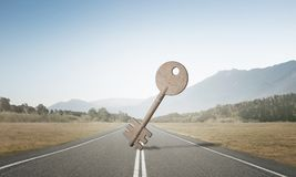 Conceptual background image of concrete key sign on asphalt road. Key stone figure as symbol of access outdoor against natural landscape Stock Photos