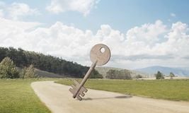 Conceptual background image of concrete key sign on country road. Key stone figure as symbol of access outdoor against natural landscape Stock Photography