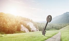 Conceptual background image of concrete key sign on green field. Key stone figure as symbol of access outdoor against natural landscape Stock Photos