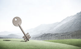 Conceptual background image of concrete key sign and natural lan. Key stone figure as symbol of access on green hill Royalty Free Stock Photo