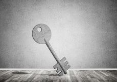 Conceptual background image of concrete key sign in room with wo. Key stone figure as symbol of access in empty concrete room Royalty Free Stock Photos