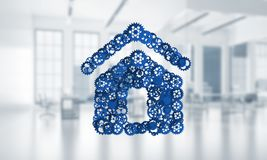 Real estate or construction idea presented by home icon on white office background. Conceptual background image with house sign made of connected gears. 3d Royalty Free Stock Images