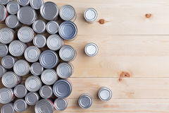 Conceptual background of multiple canned foods. For food drive donations in sealed aluminum tins or cans of varying sizes arranged on a wooden table with copy stock image