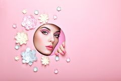 Conceptual beauty portrait of beautiful young woman. Face of Girl with Spring Pink Make-up. Beauty Fashion Model Woman Face perfect Skin. Paper Flowers on Pink Stock Images