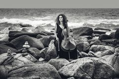beautiful young woman playing cello on stone beach at stormy weather stock photos