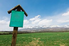 Conceptual blank sign of green color in front of mountains royalty free stock photo