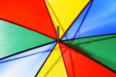 Creative concept of a bright multicolored beach umbrella closeup. Conceptual bright multicolored beach umbrella closeup Stock Image