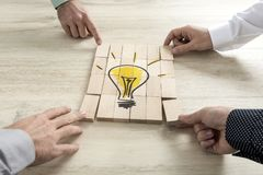 Conceptual of business strategy, creativity or teamwork. Four businessmen holding pieces of a wooden bricks bearing the image of a light bulb conceptual of stock image