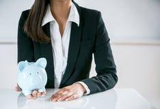 Conceptual Businesswoman Holding a Piggy Bank Stock Images