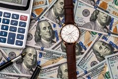 Conceptual clock, calculator on the background. Of dollar bills Royalty Free Stock Images