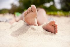 Close up of beautiful young woman feet taking sun bath on the be stock image