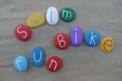 Swim, run, bike, three sports of triathlon, text words with colored stones over beach sand Stock Illustration