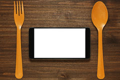 Conceptual composition with cell and cutlery. Cell phone or tablet between fork and spoon concept for delivery or any other meals service or mobile application royalty free stock image