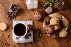 Conceptual composition with two jars of coffee beans, instant coffee and tasty cookies on wooden table, selective focus Royalty Free Stock Photography