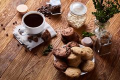 Conceptual composition with two jars of coffee beans, instant coffee and tasty cookies on wooden table, selective focus Royalty Free Stock Images