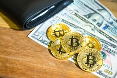 Conceptual cryptocurrency bitcoin with wallet on table with US D. Conceptual cryptocurrency bitcoin with wallet on wooden table with US Dollar bill Stock Photos