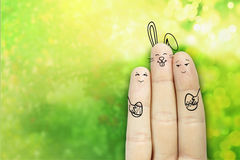 Conceptual easter finger art. Couple with a bunny are holding painted eggs. Stock Image. Creative and funny love series. Painted fingers family concept stock photography