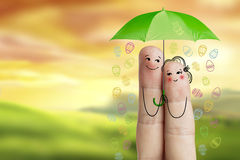 Conceptual easter finger art. Couple is  holding green umbrella with falling easter eggs. Stock Image Royalty Free Stock Photography