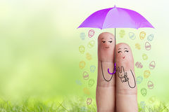 Conceptual easter finger art. Couple is holding violet umbrella with falling easter eggs. Stock Image Stock Image