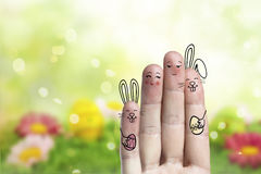 Conceptual easter finger art. Couple with a two bunnys are holding painted eggs Stock Photo