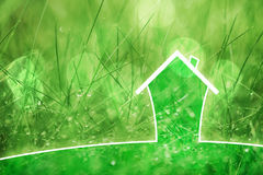 Conceptual eco home on rainy grass background. Eco healthy house concept on blurred rainy grass copy space background Stock Image