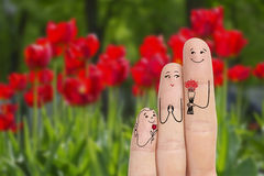 Conceptual family finger art. Father and daughter are giving flowers his mother. Stock Image. Happy Mother's Day, birthday and 8 March creative and funny love Royalty Free Stock Image