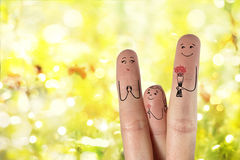 Conceptual family finger art. Father and daughter are giving flowers his mother. Stock Image Royalty Free Stock Images